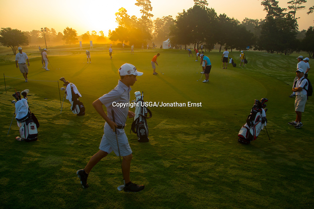 Players warm up on the practice green during the first round of stroke play of the 2014 U.S. Junior Amateur at The Club at Carlton Woods in The Woodlands, Texas.