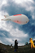 Launching weather balloon with field mills into storm. Balloon is 1500 cubic feet surplus nylon with fins that is tethered and carries an electronic field meter. Langmuir Atmospheric Research Lab on Mt. Baldy, New Mexico (1992)