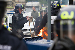 © Licensed to London News Pictures. 14/07/2012. Bristol , UK . Anti fascist protesters clash with police as they attempt to block the route for EDL supporters to leave their demontration . The anti fascists turn over wheelie bins and set them alight . The English Defence League hold a march and demonstration in Bristol . Photo credit : Joel Goodman/LNP