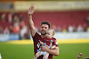 Northampton Town defender David Buchanan (3) carries his baby son and applauds the fans at the end of the EFL Sky Bet League 1 match between Northampton Town and Oldham Athletic at Sixfields Stadium, Northampton, England on 5 May 2018. Picture by Dennis Goodwin.