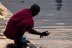 "India, Nasik, 2006. Newly shaven, a pilgrim cleans himself before ""puja"" in the Ramkund, which holds water from the Godavari River."