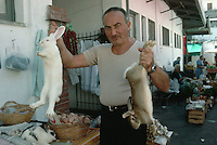 November 1989, Ischia, Italy --- Street Vendor Holding Rabbits for Sale --- Image by ? Owen Franken