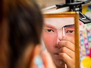 "14 MAY 2015 - BANGKOK, THAILAND:  A performer puts on her makeup before going on stage at the Pek Leng Keng Mangkorn Khiew Shrine in the Khlong Toey slum in Bangkok. Chinese opera was once very popular in Thailand, where it is called ""Ngiew."" It is usually performed in the Teochew language. Millions of Chinese emigrated to Thailand (then Siam) in the 18th and 19th centuries and brought their culture with them. Recently the popularity of ngiew has faded as people turn to performances of opera on DVD or movies. There are still as many 30 Chinese opera troupes left in Bangkok and its environs. They are especially busy during Chinese New Year and Chinese holiday when they travel from Chinese temple to Chinese temple performing on stages they put up in streets near the temple, sometimes sleeping on hammocks they sling under their stage. Most of the Chinese operas from Bangkok travel to Malaysia for Ghost Month, leaving just a few to perform in Bangkok.      PHOTO BY JACK KURTZ"
