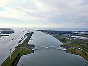 Nederland, Zuid-Holland, Hoek van Holland, 14-09-2019; Nieuwe Waterweg, Haven van Rotterdam. Functioneringssluiting Maeslantkering. De waterkering in de Nieuwe Waterweg wordt een maal per jaar, voordat het stormseizoen begint, getest. Tijdens het sluiten van de kering ligt alle scheepvaartverkeer naar de Rotterdamse haven stil. Links Callandkanaal en de havens van Europoort, aan de horizon ingan van de Nieuwe Waterweg en de Noordzee.  De Maeslantkering sluit normaal gesproken alleen bij dreigende stromvloed en bij een waterstand van 3 meter of meer boven NAP. De kering, onderdeel van de Deltawerken, vormt samen met de Hartelkering de Europoortkering en beschermt Rotterdam en achterland bij extreme waterstanden.<br /> Hook of Holland - Port of Rotterdam. Aerial view of the new storm surge barrier (Maeslantkering) in the Nieuwe Waterweg during the so-called functioning closure, taking place one a year before the storm season begins. The waterway, leading to the Port of Rotterdam (at the horizon), is closed during the test. <br /> luchtfoto (toeslag op standard tarieven);<br /> aerial photo (additional fee required);<br /> copyright foto/photo Siebe Swart