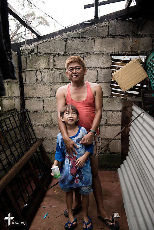 Leonardo Lopez stands for a portrait with his son Danly, 7, at his home in Tacloban, Leyte Province, Philippines, on Friday, March 14, 2014. Lopez cradled his son behind the door as rain and winds from Typhoon Haiyan lashed against his home. LCMS Communications/Erik M. Lunsford