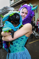 "23 Feb 2014. New Orleans, Louisiana.<br /> Jessica Edrington and her dog Lucy walk the wet and soggy streets of the French Quarter at the 22nd Mystic Krewe of Barkus parade, the only officially licensed Mardi Gras krewe by and for canines. This year's parade is themed  ""Dogzilla: Barkus Licks the Crescent City."" <br /> Photo; Charlie Varley/varleypix.com"