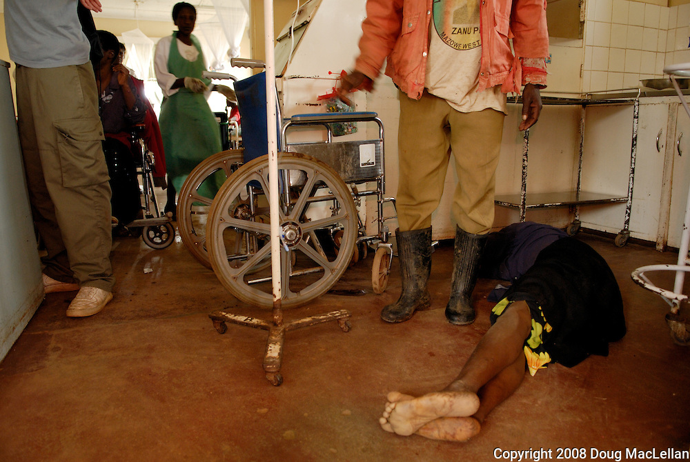Howard Hospital, Zimbabwe. December 14, 2008. A woman in her late twenties, early thirties lies on the hospital floor as her husband stands over her. She is in the process of a spontaneous abortion.