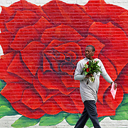 Clifton Howard of Kansas City, Mo. made a stop after his workday at House of Flowers at 601 E. 31st Street in midtown to pick up a bouquet of flowers for his wife as a surprise on Valentine's Day Monday afternoon. He picked out a vase of lilies and roses for his wife of 19 years. The florist has a large floral mural painted on the side of the store.