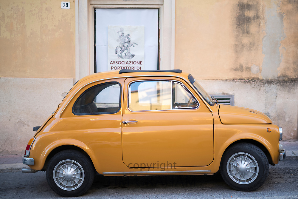 Bright yellow colour Fiat 500 Cinquecento- typical Italian small city car - in ancient Modica Alta, Sicily