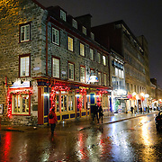 Street at night in Quebec City's Old Town after drizzle that creates a wet sheen on the cobblestone roadway.