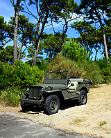 "Unmanned WW2 or WWII Jeep Willis in excellent condition parked on sand. This vehicle has lived a 'revival' and recently has come very much ""en vogue"" as a 'casual summer caddy' among wealthy people in this part of France."