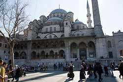 Locals and tourists pass Yeni Cami, or New Mosque, in the Eminonu area of Istanbul, Turkey.