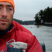 "4/27/11 -- BRUNSWICK, Maine. Eliot Pitney, Coach of Bowdoin Women's Crew, drills his team on the new Meadows river in late April. Pitney has coached at Bowdoin for the last 4 years. and before that at Bates.  ""This time of year,"" he says, "" I'm ready to quit -- I'm just exhausted. But, give me a week off and then I'm right back at it -- ready to go for fall!""  Pitney, also working on a  Master's in Mechanical Engineering puts in about 12 hours a week on the water - not including trips to and from races. ""It gets in your blood,"" he says of rowing. ""You love it or hate it. . .""   Photo by Roger S. Duncan."