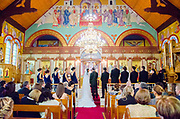 Greek orthodox wedding with bride and groom and bridal party at front. Bride and groom are wearing crowns.
