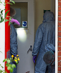 © Licensed to London News Pictures. 27/07/2015. London, UK. Forensics officers examine blood marks on an interior door at the property. Police and scene of crime officers at Collette House in Acton, West London, where the body of a woman in her 30s was found this morning (Mon). Police are currently searching for Michael Meanza  aged 47 in connection with the death.  Photo credit: Ben Cawthra/LNP