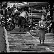 A young novice Buddhist monks makes his rounds in Mae Sot, Thailand.  Thailand is predominately Buddhist nation.  (Photo by David Longstreath)
