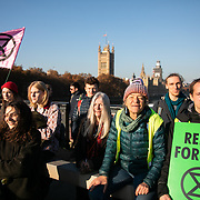 Thousands of Extinction Rebellion activists took over 5 bridges in Central London and blocked them for the day, November 17 2018, Central London, United Kingdom. Lambeth Bridge; Around 11am people on all bridges sat down in the road and blocked traffic from coming through and stayed till late afternoon. The actvists believe that the government is not doing enough to avoid catastrophic climate change and they demand the government take radical action to save future generations and the planet. Many are willing to be arrested peacefully protesting and up to 80 were arrested on the day.Extinction Rebellion is a grass root climate change group started in 2018 and has gained a huge following of people commited to peaceful protests and who ready to be arrested. Their major concern is that the world is facing catastropohic climate change and they want the British government to act now to save future generations.