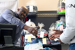 Customer is greeted with the smile of James Betterson, former Philadelphia Eagles Running Back and owner of BetterClean Laundry in NorthEast Philadelphia, on February 15, 2019. Betterson, graduated of the free Power Up Your Business training program will testify next week in city council during a hearing to determine if the program will get extended funding. (Bastiaan Slabbers for WHYY)