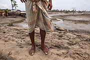 A villager stands on solid ground amid the shifting sands and water of southern Bangladesh.
