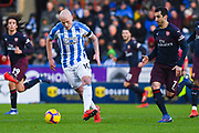Aaron Mooy of Huddersfield Town (10) passes the ball under pressure from Henrikh Mkhitaryan of Arsenal (7) during the Premier League match between Huddersfield Town and Arsenal at the John Smiths Stadium, Huddersfield, England on 9 February 2019.