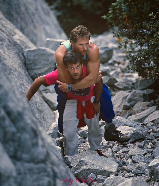 Mike Corbett carries Mark Wellman to the beginning of the Shield Route on El Capitan.  July 1989..Wellman became the first paraplegic climber to ascend the 3000' granite monolith during an eight-day climb.