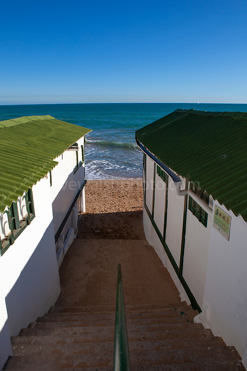 Platja de Les Casetes del Garraf, Garraf, Barcelona, Catalonia. These distinctive small green and white beach houses are in the beach village of Garraf, not from Barcelona. They re listed under the Patrimonio Cultural Catala. No one is sure how they came about - small houses for beachgoers or fishermens huts - either way, they were established in the early 20th century.