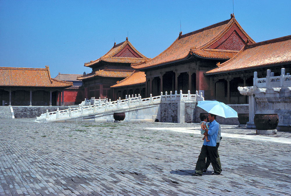 Visitors shield themselves from the bright sun in the courtyard of the Forbidden City, Beijing, China.