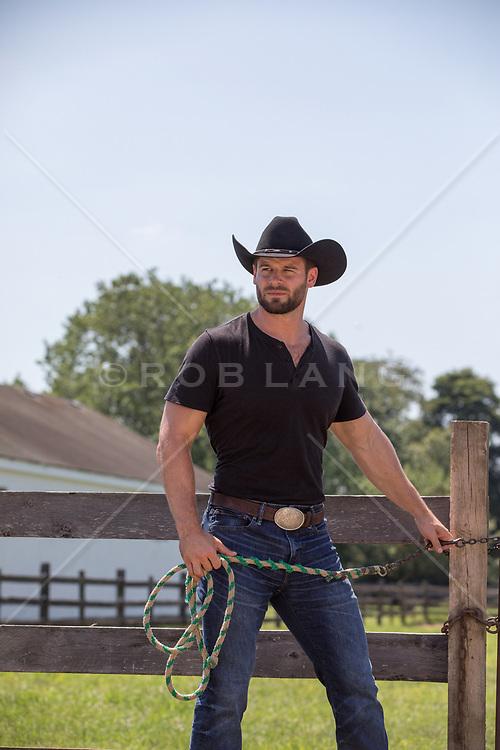 rugged cowboy opening up a barn door rugged cowboy on a ranch