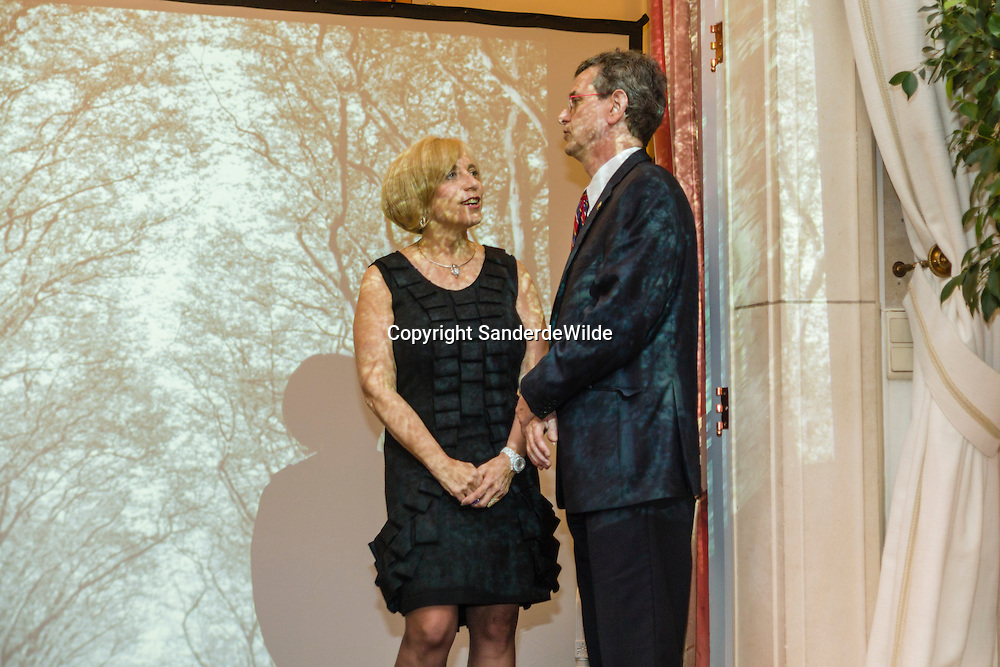 2011-03-31, Brussels, Belgium, Embassy of the United States of America:  Dr. Michelle Loewinger (left) talks to her husband US ambassador Howard Gutman at a party held in the embassy. A projection of slides cover them and the background.