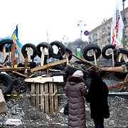 December 18, 2013 - Kiev, Ukraine: Local women look at a barricade in Independence Square.<br /> On the night of 21 November 2013, a wave of demonstrations and civil unrest began in Ukraine, when spontaneous protests erupted in the capital of Kiev as a response to the government's suspension of the preparations for signing an association and free trade agreement with the European Union. Anti-government protesters occupied Independence Square, also known as Maidan, demanding the resignation of President Viktor Yanukovych and accusing him of refusing the planned trade and political pact with the EU in favor of closer ties with Russia.<br /> After a days of demonstrations, an increasing number of people joined the protests. As a responses to a police crackdown on November 30, half a million people took the square. The protests are ongoing despite a heavy police presence in the city, regular sub-zero temperatures, and snow. (Paulo Nunes dos Santos/Polaris)