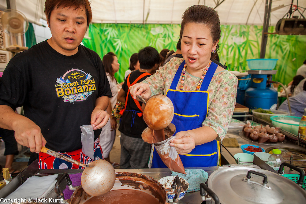 17 OCTOBER 2012 - BANGKOK, THAILAND:  Vendors serve a vegan drink in the courtyard at Wat Mangkon Kamalawat, one of the largest Chinese shrines in Thailand, during the Vegetarian Festival.  The Vegetarian Festival is celebrated throughout Thailand. It is the Thai version of the The Nine Emperor Gods Festival, a nine-day Taoist celebration celebrated in the 9th lunar month of the Chinese calendar. For nine days, those who are participating in the festival dress all in white and abstain from eating meat, poultry, seafood, and dairy products. Vendors and proprietors of restaurants indicate that vegetarian food is for sale at their establishments by putting a yellow flag out with Thai characters for meatless written on it in red.      PHOTO BY JACK KURTZ