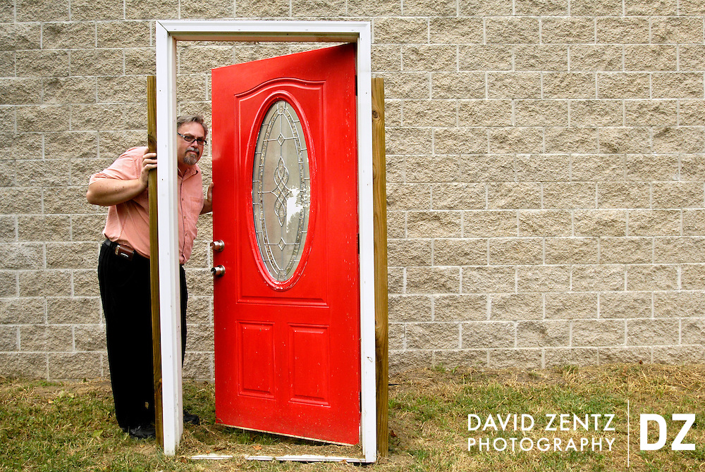 Phil Doubet show's off a fake door positioned in front of his minimalist home in Hanna City, Ill. There is no actual front door on the home, which must be entered on the second floor.