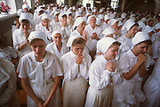 Ukranian women pray before being baptized in the river in Lviv, Ukraine.