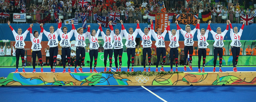RIO DE JANEIRO, BRAZIL - AUGUST 19:  Team Great Britain pose on the podium during the medal ceremony after defeating Netherlands in the Women's Gold Medal Match on Day 14 of the Rio 2016 Olympic Games at the Olympic Hockey Centre on August 19, 2016 in Rio de Janeiro, Brazil.  (Photo by Tom Pennington/Getty Images)