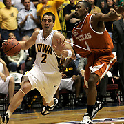 Iowa guard Jeff Horner pulls Texas guard Daniel Gibson along the baseline after hooking his finger on the drawstring of Gibson's shorts.  Horner's finger remained there all the way to the basket, even after his shot was swatted away.  The action took place in the Guardian Classic in Kansas City when the two teams met in the championship game at old Municipal Auditorium.  Both players were among the 50 finalists for the John Wooden award, given at the end of the season to the collegiate player of the year.