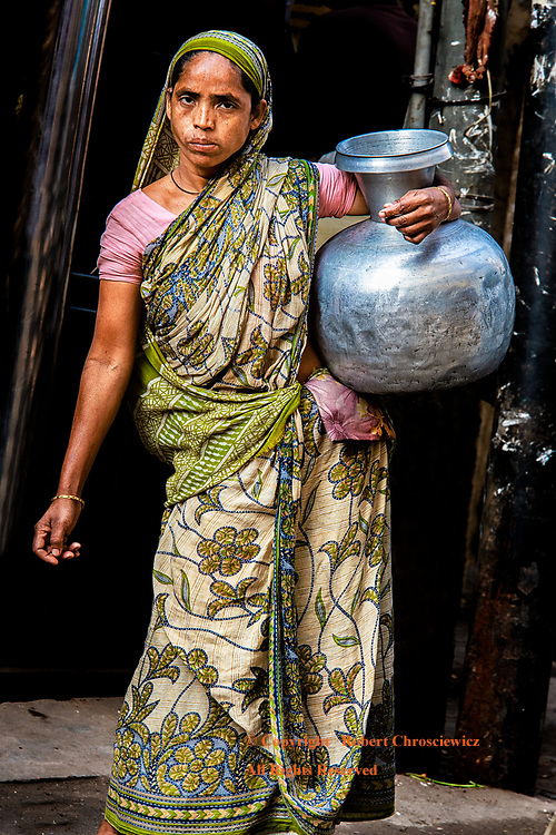 Water Carrier: A woman in traditional dress ventures out onto the street with a metal vase filled with water, Dhaka Bangladesh.