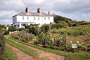 Houses and gardens at Dunwich, Suffolk. The furthest one is abandoned because of the risk of cliff erosion.