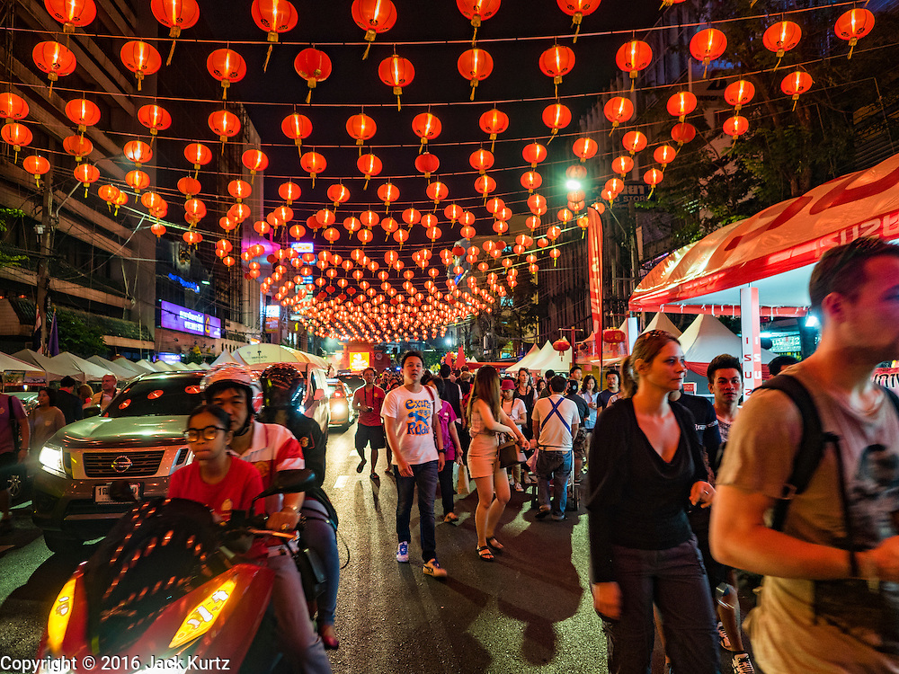 "07 FEBRUARY 2016 - BANGKOK, THAILAND:  Chinese New Year lanterns hang over people on Yaowarat Road, the heart of Bangkok's Chinatown. Chinese New Year, also called Lunar New Year or Tet (in Vietnamese communities) starts Monday February 8. The coming year will be the ""Year of the Monkey."" Thailand has the largest overseas Chinese population in the world; about 14 percent of Thais are of Chinese ancestry and some Chinese holidays, especially Chinese New Year, are widely celebrated in Thailand.        PHOTO BY JACK KURTZ"