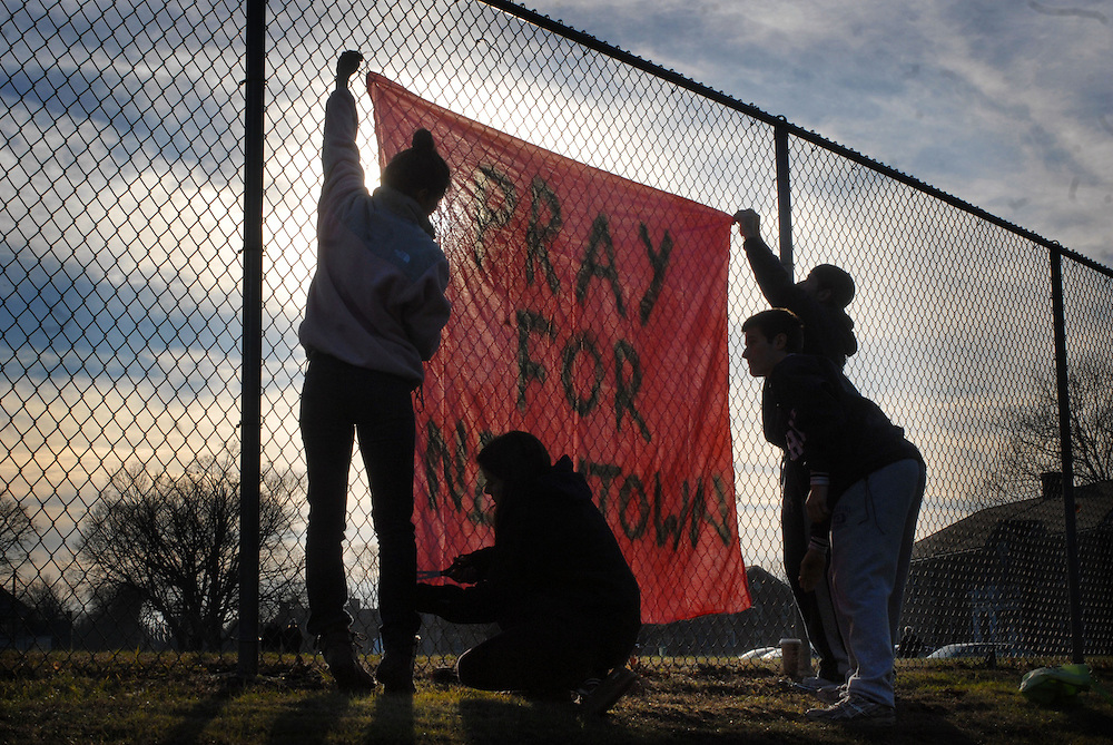 "24 hours after a shooting that killed 20 children and 6 adults at Sandy Hook Elementary School Ryan Martin, 24, his Brother Brendan, 22, Colleen Thornberg, 22 and Christie Attanasio,22, from Newtown  pin a banner to a fence in Newtown. It says ""Pray for Newtown."""