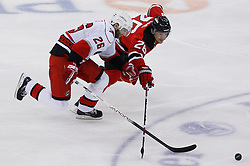 Apr 23, 2009; Newark, NJ, USA; Carolina Hurricanes right wing Erik Cole (26) and New Jersey Devils left wing Patrik Elias (26) battle for the puck during the third period of game five of the eastern conference quarterfinals of the 2009 Stanley Cup playoffs at the Prudential Center. The Devils beat the Hurricanes 1-0 to take a 3-2 lead in the best of 7 series.