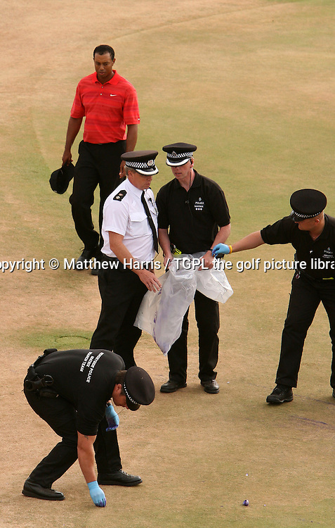 Tiger WOODS (USA) arrives on the 18th green as police officers clean up purple flower bombs thrown onto the 18th green during fourth round The Open Championship 2006,Royal Liverpool,Hoylake,Whirral,England.The bombs were thrown just as Woods approached the 18th green for  his final shot of the tournament.It is believed that the missiles were thrown by a splinter section of the now defunct Fathers 4 Justice group.<br /> <br /> EPA/Pool