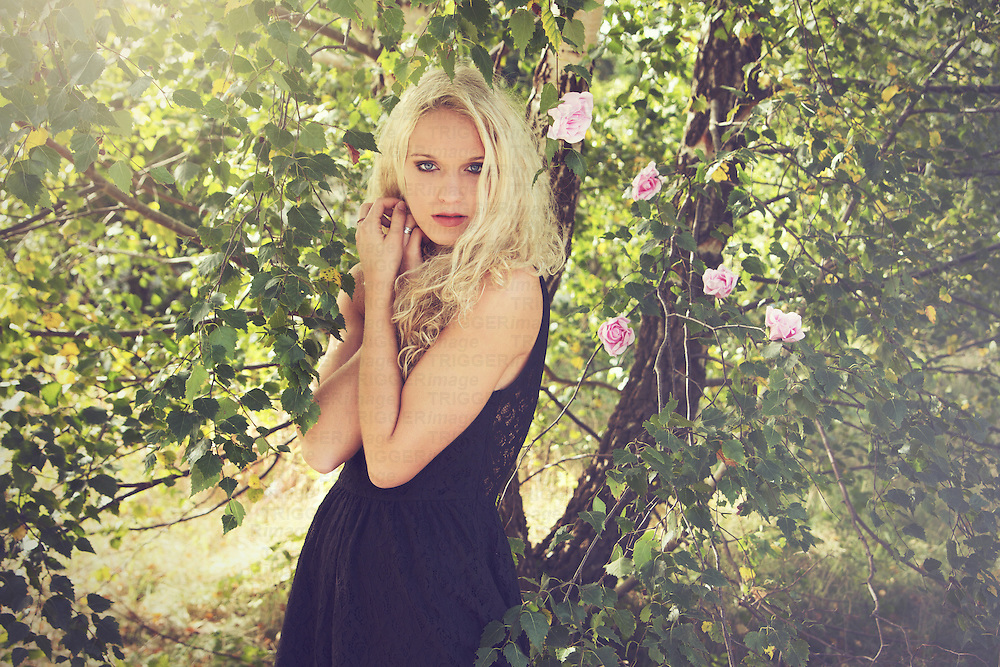 Young woman wearing a black lace dress and facing the camera outside the nature