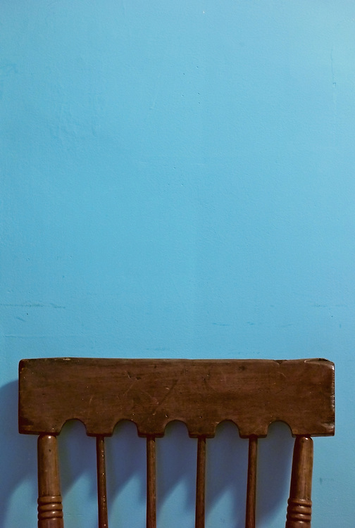 Antique chair back against blue wall
