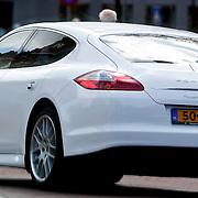 NLD/Laren/20100422 -  Gordon Heuckeroth in Laren rijdend in zijn witte Porsche Panamera