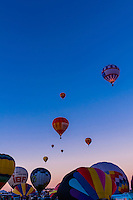Hot air balloons lifting off at sunrise, Albuquerque International Balloon Fiesta, Albuquerque, New Mexico USA.