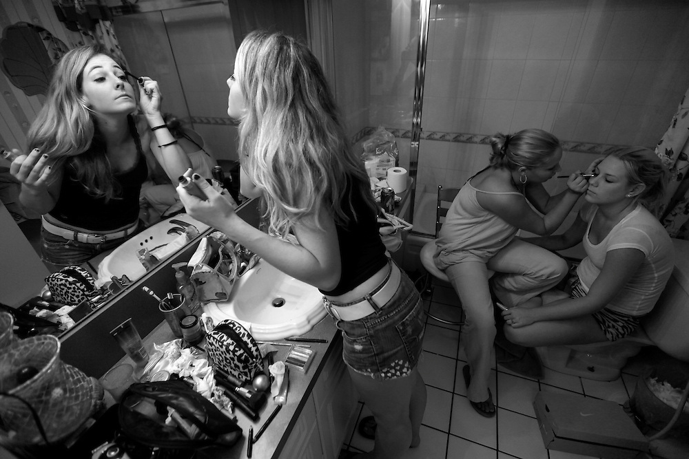 """Elaine Neal prepares to go to a """"Pimps and Hos"""" party while friends Amber Auckerman, 18, right, has makeup put on by Kristine Beaver, 18, center. Neal, a former beauty pageant contestant, loved to get dressed up and be, as she said, a """"girly-girl."""" But she also loved the no frills nature of the US Marine Corps. """"Comparing my personality to what I'm doing seems like something that's completely opposite,"""" Neal said. Greg Kahn/Staff"""