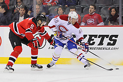 Feb 2; Newark, NJ, USA; Montreal Canadiens right wing Andrei Kostitsyn (46) is defended by New Jersey Devils defenseman Adam Larsson (5) during the third period at the Prudential Center. The Devils defeated the Canadiens 5-3.