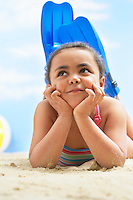 Girl (7-9 years) wearing flippers lying on stomach on beach