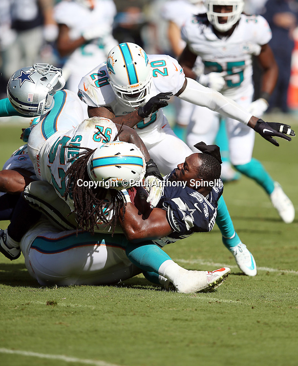 Dallas Cowboys running back Robert Turbin (23) loses his helmet on a gang tackle by Miami Dolphins middle linebacker Kelvin Sheppard (52) and Miami Dolphins linebacker Neville Hewitt (46) on a second quarter run during the 2015 week 11 regular season NFL football game against the Miami Dolphins on Sunday, Nov. 22, 2015 in Miami. The Cowboys won the game 24-14. (©Paul Anthony Spinelli)