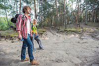 Full length of hiking couple walking in forest